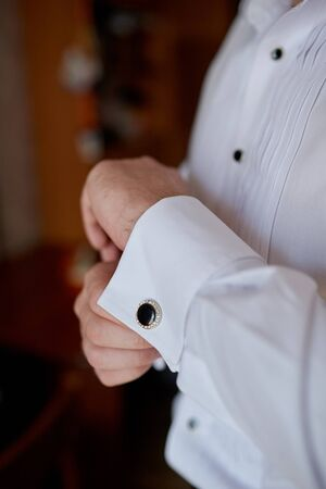 man in the white shirt near the window dress cufflinks. Stock Photo
