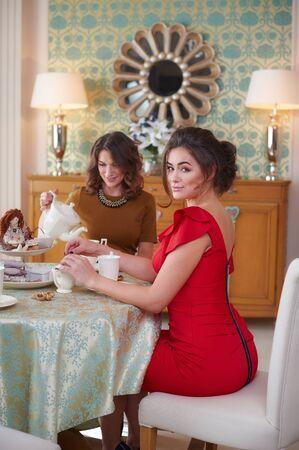 conflictos sociales: Dos mujeres en la cocina bebiendo t�. Foto de archivo