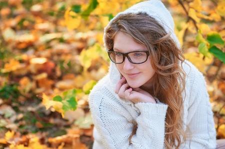 sueteres: mujer joven con gafas de sol caminando en el parque otoño.