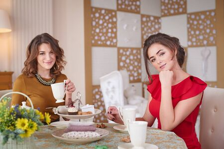 squabble: Two women in the kitchen drinking tea.
