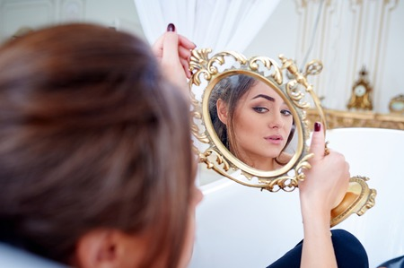 on mirrors: beautiful woman in the bathroom looking in the mirror. Stock Photo
