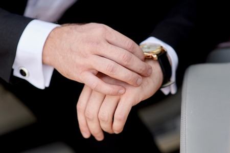 punctuality: Businessman looking at his watch punctuality. Stock Photo
