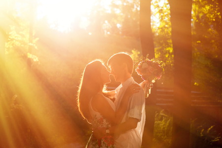 young couple hugging kissing: groom is holding and kissing his  bride on the background sunset. Stock Photo