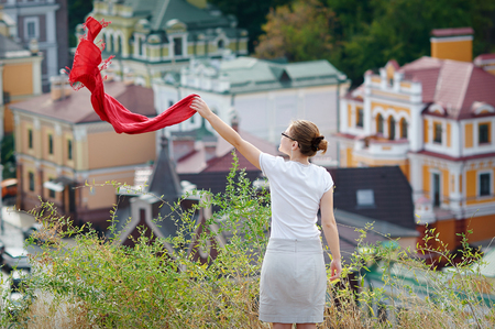 red scarf: woman standing on the hill and waving a red scarf.