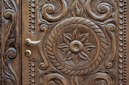ornately: beautiful ornately carved wooden panel in an antique door.