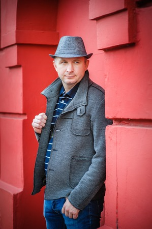 nonchalant: man in a hat near the red wall. Stock Photo