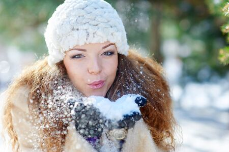 beautiful woman in winter blows snow with hands.