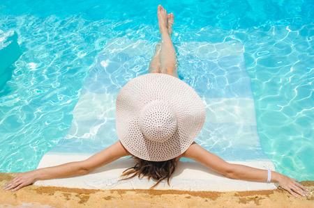 수영장에서 휴식 큰 whire 모자 여자. 여행 스파 리조트 수영장에서 여자입니다. 여름 럭셔리 휴가. 스톡 콘텐츠