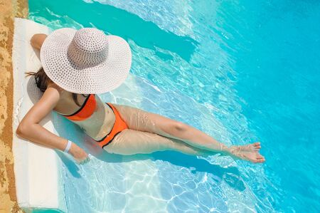 Woman in big whire hat relaxing on the swimming pool. Girl at travel spa resort pool. Summer luxury vacation.
