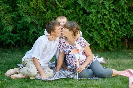 ragazza innamorata: Famiglia di padre madre e bambino, genitore baciare a vicenda e bambino sorridente e abbracci. Archivio Fotografico