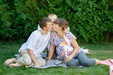 flowers boy: Family of mother father and boy, parent kissing at each other and little boy smiling and hugging.