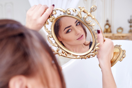 Woman Looking At Herself In The Mirror. Stock Photo