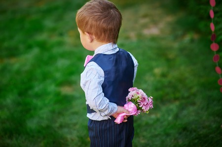 beautiful little boys: Little boy holding a bouquet of flowers behind his back. Stock Photo