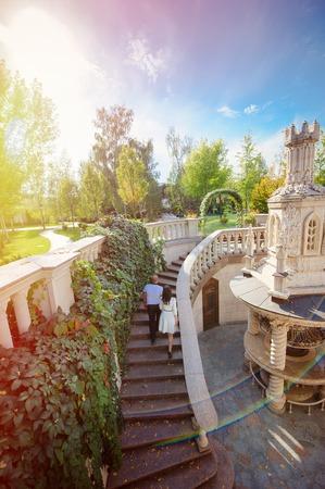 backview: UKRAINE, KIEV, MEJIGORIE, SEPTEMBER, 24, 2015: couple walk up to stairs and holding hands. backview Stock Photo