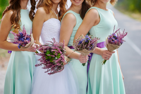minx: bride and bridesmaids are showing beautiful flowers on their hands.