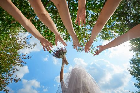 bride bouquet: bride throws the bouquet to unmarried girls Wedding Traditions. Stock Photo