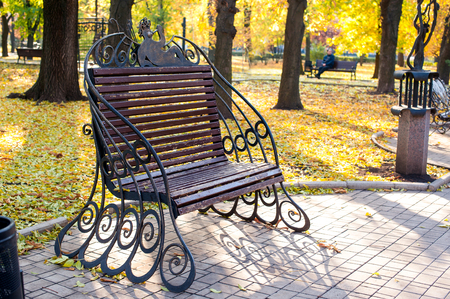 quick hedge: beautiful forged metal bench in the autumn park.