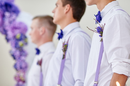 groomsmen stand on a wedding ceremony.