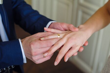 fingers put together: Groom wears bride a gold ring on her finger. Stock Photo