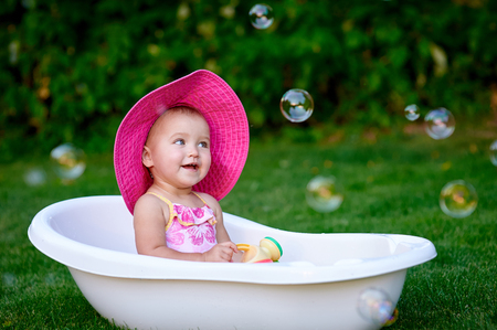pink hat: beautiful little girl bathes in summer pink hat.
