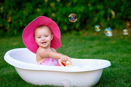 12 year old: Baby girl 1-2 year old taking bath with soap foam outdoors. Childhood. Washing Stock Photo