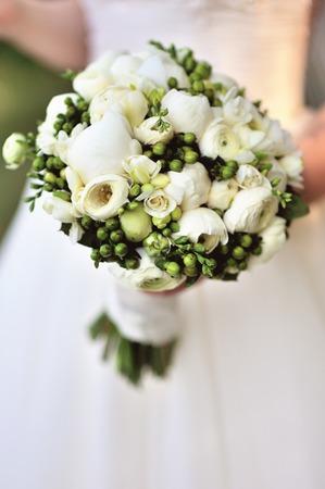 свадьба: Красивый белый свадебный букет в руках невесты