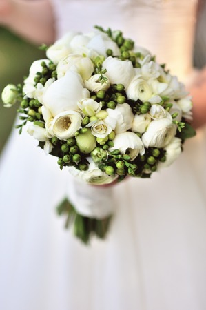 reception desk: Beautiful white wedding bouquet in hand of bride