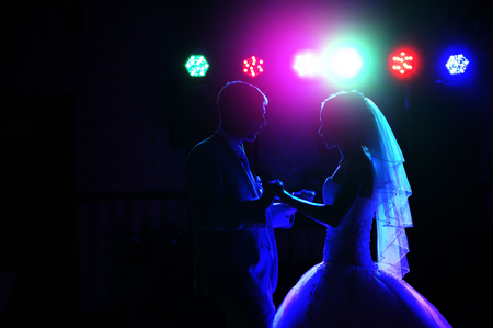 Kiss and dance young bride and groom in dark banqueting hall