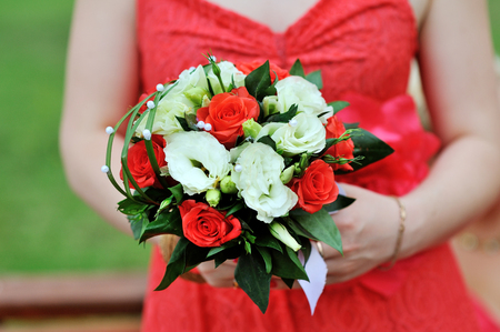 red dress: Bride in red dress holding wedding bouquet