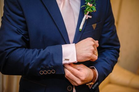 wrist cuffs: groom in a suit hands wear cufflinks in room. Stock Photo