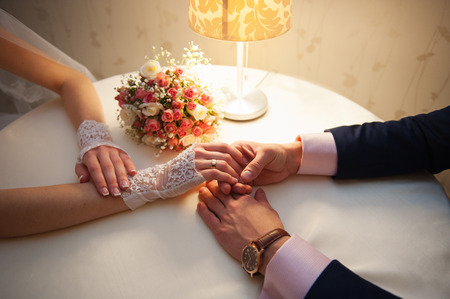 stroking: bride and groom are sitting at a table in restaurant. The grooms hand stroking his bride