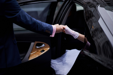 give out: groom give hands bride out from wedding car.