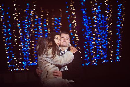 corazones azules: amantes felices abrazan sobre un fondo de brillantes corazones azules.