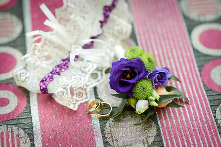 wedding accessories: Wedding accessories brides garter, rings and boutonniere. Stock Photo