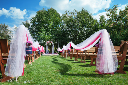 entrance arbor: Wedding benches with flower arch for ceremony outdoors.