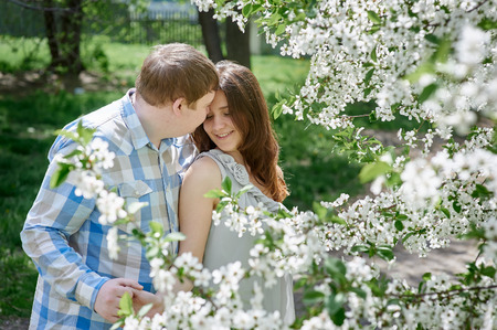 parejas enamoradas: Attractive young couple on a spring garden walk in the countryside in front of a tree covered in white blossom Foto de archivo