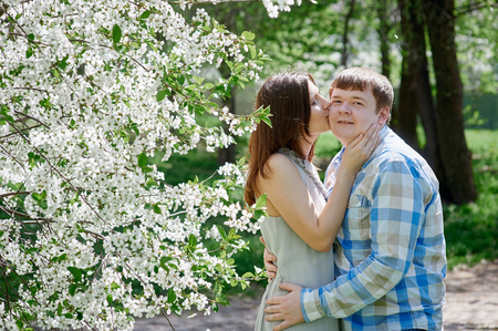 tenderness: Love and tenderness. woman kissing a man in the blossoming spring garden Stock Photo
