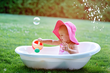 female in douche: Little girl sitting in a bathtub with soap bubbles.