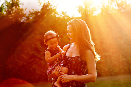 suns: Mom holds daughter on the hands and on the background of the suns rays