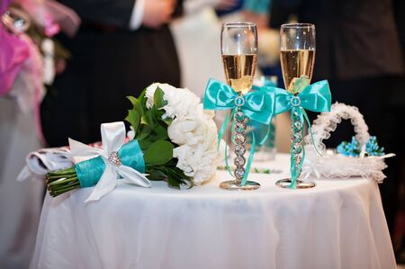 wedding table decor: Glasses of champagne and wedding bouquet and on the table. Stock Photo