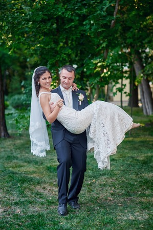 his: groom holds his bride in his arms and smiles of happiness.