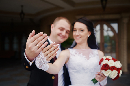 alliance: happy bride and groom showing their rings on hands.