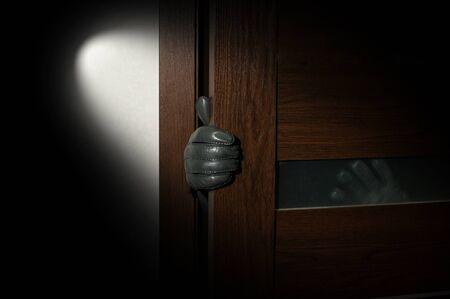 prowler: mans hand in a black glove open the door. Stock Photo