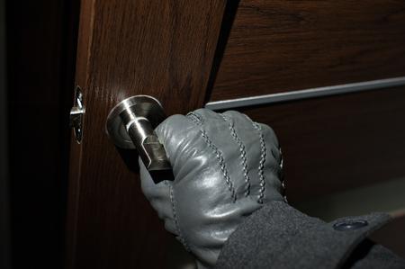 doorlock: mans hand in a black glove opening the door.