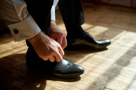 white suit: Business man tying shoe laces on the floor. Close-up.