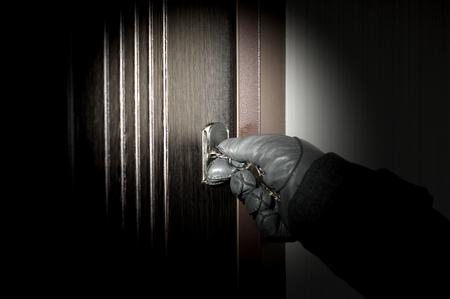 villain: Villain opens the apartment burglary at night. Stock Photo