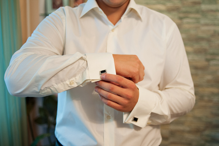 cuffs: man wears cufflinks on French cuffs sleeves luxury white shirt.
