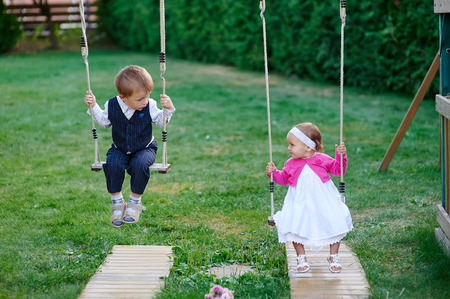 playground ride: little boy and girl ride on a swing at the playground in the park. Stock Photo