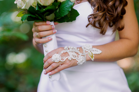 lace gloves: Brides hands with manicure in white lace gloves.