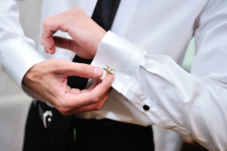 french cuffs: man in white shirt near window dress cufflinks.